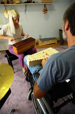 άνδρας-σε-αμαξείδιο-παίζει-ξυλόφωνο-σε-συνεδρία-μουσικής-ψυχοθεραπείας